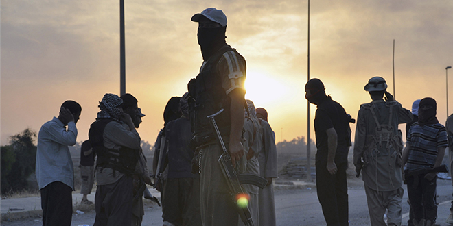 """Islamic discussion: Islamic State fighters stand guard at a checkpoint in the northern Iraqi city of Mosul. The United Nations reported that the Islamic State had committed a """"staggering array"""" of human rights abuses and """"acts of violence of an increasingly sectarian nature"""" in Iraq. Photo: CNS"""
