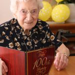 Treasured ministry: Presentation Sister Peggy Dolan with a special card containing pages of well-wishes from those attending her recent 100th birthday party at Nudgee's Emmaus Retirement Village. Photo: Paul Dobbyn