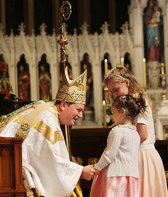 First meetings: Archbishop Anthony Fisher greets some young children at his installation Mass in St Mary's Cathedral, Sydney, on Wednesday, November 12.