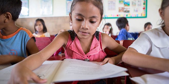 Back to school: Mary Faith, one of the thousands affected by Typhoon Haiyan, is back in the school classroom and back to life almost as normal, thanks to help from Caritas.Photo: Caritas Australia