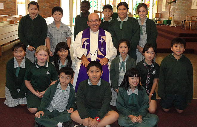 Praying for their shepherd: Divine Word Missionaries Father Gerard Mulholland with students from St Mark's Catholic Primary School, Inala, after a Mass at the school.