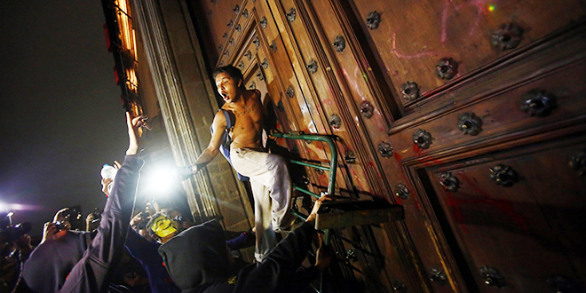 Mexican unrest: A protester climbs up a barricade leaning on the timber door of Mexican President Enrique Pena Nieto's ceremonial palace, during a protest denouncing the massacre of 43 trainee teachers. The door was later set on fire. Photo: CNS