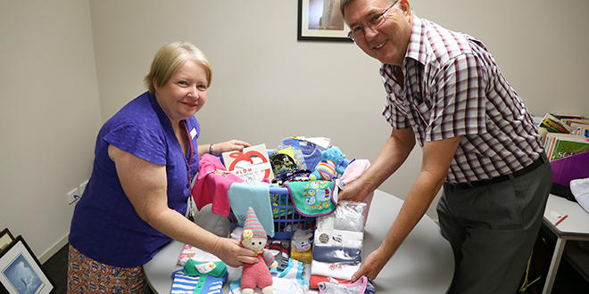 Time to give: Carmel Carden and Michael Bruynesteyn with a small portion of the items staff at Queen of Apostles Catholic primary School have donated to support an Iranian refugee couple awaiting the birth of a child in Brisbane. Photo: Emilie Ng