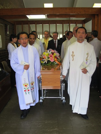 Farewell: Fr Gerard Mulholland's coffin is processed from St Mark's Church, Inala, by his Divine Word Missionaries confreres.