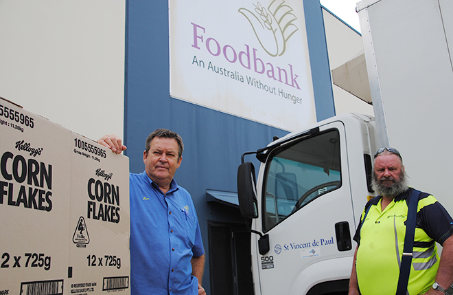 Sharing God's plenty: Gympie St Vincent de Paul Society worker Peter Kennedy (right) prepares to load weekly supplies from Foodbank Queensland with help from manager Ken McMillan. Photo: Paul Dobbyn