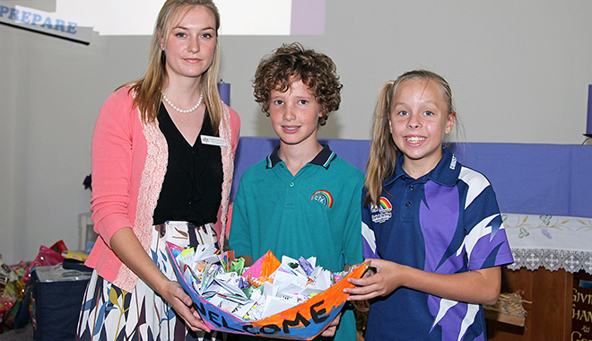 Strong message: Christ the King Catholic Primary School students Angus Watkins and Natalie Fisher present Zuzanna Kamusinski (representing Federal Member for Petrie Luke Howarth), with messages of support for refugees and asylum seekers.