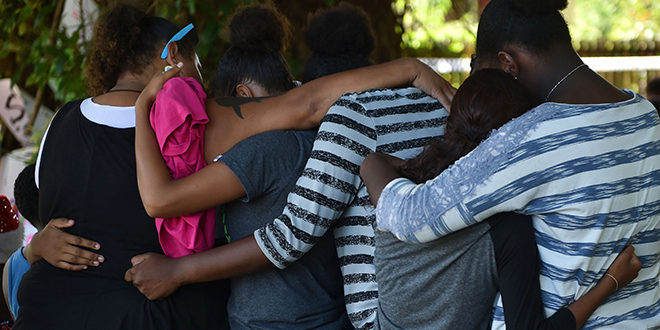 Grieving: Mourners hugging at the scene where eight children ranging from babies to teenagers were found dead in a house in Cairns. Photo: AAP