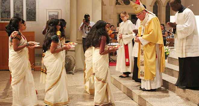 Representatives of the Brisbane Indian community in traditional dress present gifts to Archbishop Mark Coleridge during the offertory procession at Mass in St Stephen's Cathedral on the feast of St Kuriakose Elias Chavara