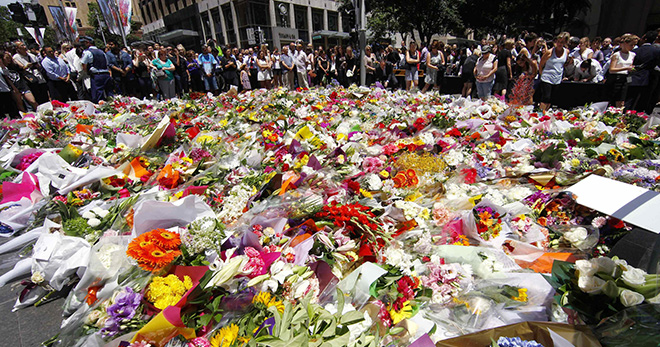 Praying for peace: Members of the public look at thousands of floral tributes placed on December 16 near the Sydney café where hostages were held for more than 16 hours. Photo: CNS
