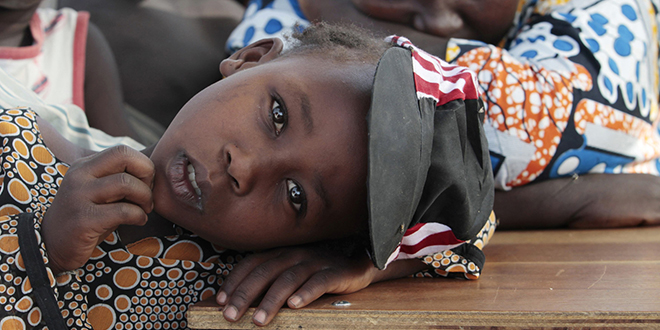 Close watch: A girl displaced as a result of Boko Haram attacks in the north-east region of Nigeria rests her head on a desk at a camp for internally displaced people in Yola. Photo: CNS/Afolabi Sotunde, Reuters