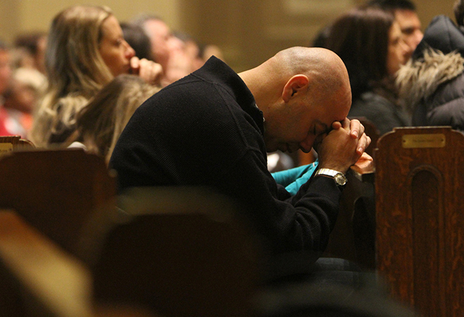 Praying for peace: A man prays during a French-language Mass at Notre Dame Church in New York on January 11. The Mass was offered for the 17 victims of the recent terror attacks in France. Photo: CNS/Gregory A. Shemitz