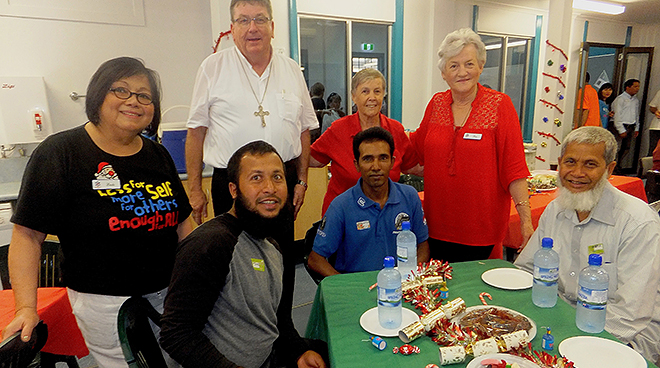 Tradition grows: Refugees (front from left) Abdul, Kamal and Safik were among those attending a Christmas Day lunch at Rockhampton's St Joseph's Cathedral. Behind them (from left) are Linda Esguerra, Bishop Michael McCarthy, Sr Pat Wood and Cr Rose Swadling.
