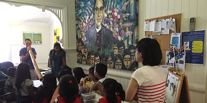 Australian welcome: Children of asylum seekers get first-hand experience of Australian culture listening to a didgeridoo at the Romero Centre. In the background is a painting of Salvadorian Archbishop Oscar Romero from whom the centre draws its name and inspiration.