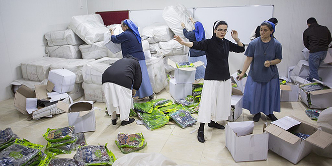 Christmas gifts: Sisters preparing Christmas parcels in Ankawa for 15,000 Christian refugee children; and (below) A young girl worshipping during Christmas Mass in Iraq. Photos: Aid to the Church in Need