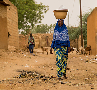 Walk of necessity: Mariama walking in the streets of Niamey selling kopto. Kopto is made from the leaves of the moringa tree. (Left) Mariama nurses her daughter Fati. Photos: Francois Therrien