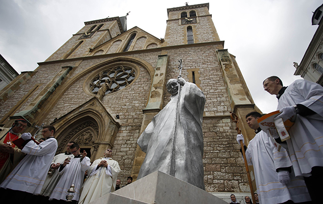 Papal visit: Clergymen stand outside a church during an unveiling ceremony of a statue of St John Paul II in Sarajevo, Bosnia and Herzegovina, on April 30 last year. The statue was erected to honour the new saint, who had called for peace during the Bosnian war of the 1990s. Photos: CNS
