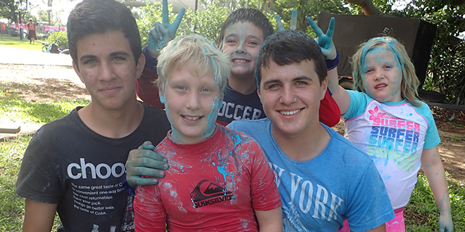 Holiday cheer: Edmund Rice Camps volunteers Jonathon Bolton and Jack Round with some of the kids from the camp.