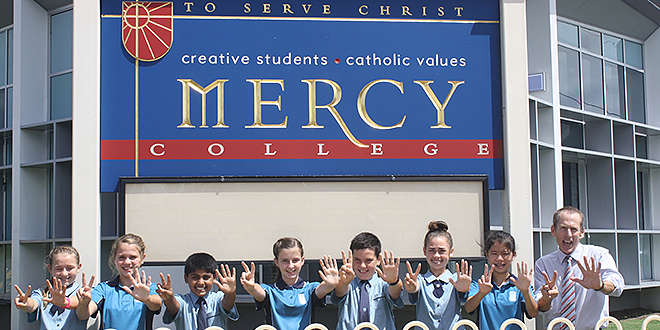 Flying start: Mercy College Mackay Year 7 students with principal Jim Ford on day one of their historic adventure in high school.