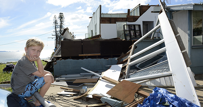 Taking stock: Tarn Smith, 7, is in front of his family's damaged home in Yeppoon on Saturday, February 21. His family had returned to inspect the damage and clean up after Cyclone Marcia had hit the day before. Photo: AAP/Karin Calvert