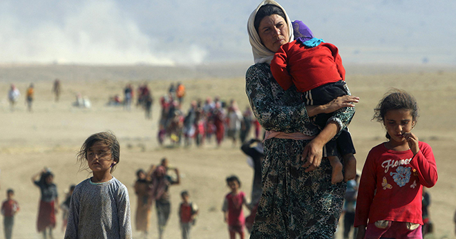 Religious persecution: Displaced people fleeing violence in Iraq walk toward the Syrian border town of Elierbeh.