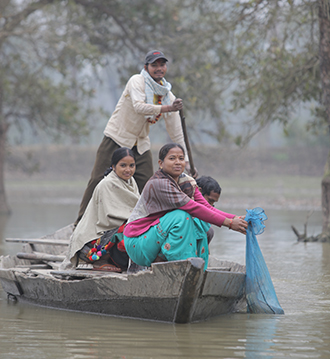 Teamwork: Sarita and other members of the Kolkatla Fish Raising Group fishing on the group's pond. The co-operative is supported by Caritas Australia.
