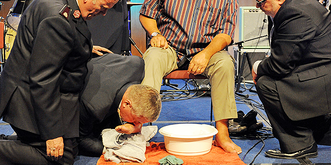 Symbolic action: Archbishop Christopher Prowse washes and kisses the feet of sexual abuse survivor Mark Stiles, assisted by Salvation Army Commissioner James Condon and Pastor Shaun Stanton of Australian Christian Churches.