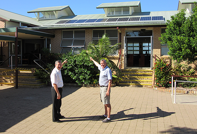 Solar switch: Caloundra parish priest Fr Kevin Smith (left) and parish services manager Don Rolls inspect some of the solar panels recently installed on the roof of Our Lady of the Rosary Church.