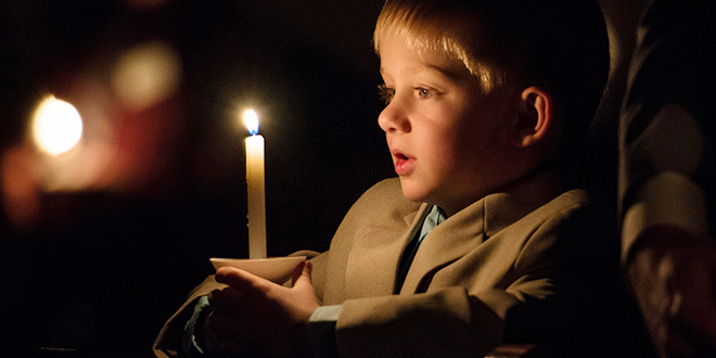 The triduum: A young boy holds a candle during the Easter Vigil. Photo: CNS