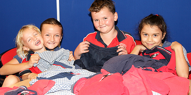 Uniform plan: St Anthony's students Tash Blank, Jasmine Blank, Tom Blank and Grace Penalosa help sort out second-hand school uniforms bound for children in the Pacific Islands.