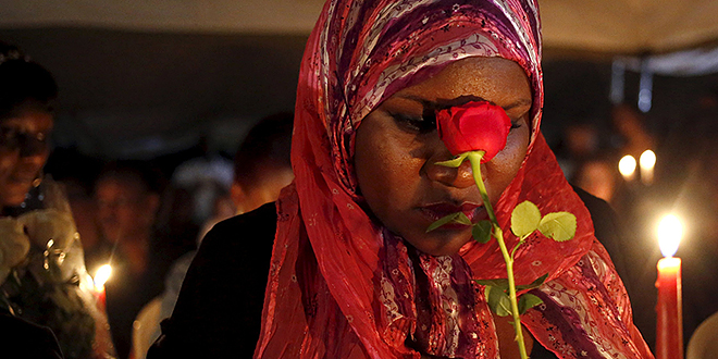 Time of prayer: A woman holds a rose as she prays during a memorial vigil in Nairobi, Kenya, April 7, for the 147 people killed in an attack on Garissa University College. Kenyan bishops are urging the government to step up security and for citizens to remain united after al-Shabab militants attacked the college campus on April 2. Photo: CNS