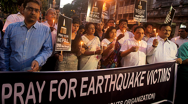 People carry a banner during an April 27 candlelight prayer service in Kolkata, India, for victims of the earthquake in Nepal. More than 3,600 people were known to have been killed and more than 6,500 others injured after a magnitude-7.8 earthquake hit a mountainous region near Kathmandu April 25. (CNS photo/Piyal Adhikary, EPA) See POPE-NEPAL April 27, 2015.