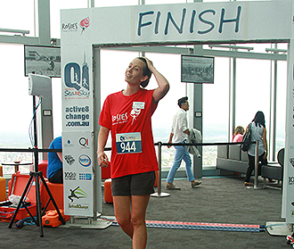 Top effort: A Rosies volunteer crosses the finish line for the inaugural Q1 Skypoint Sea to Sky Stair Climb.