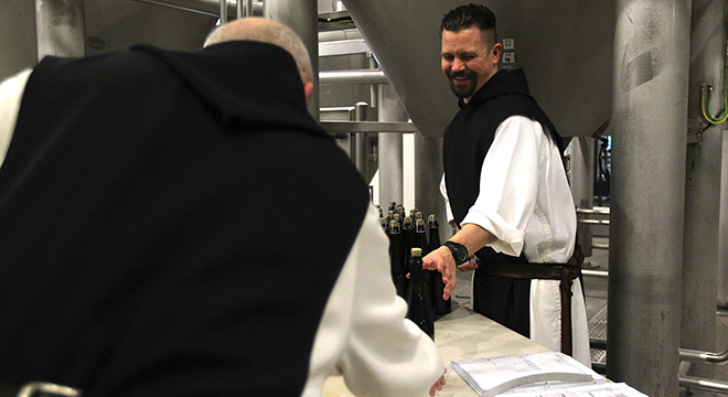 Monks' bew: Trappist Father Isaac Keeley slides a newly corked bottle of Spencer Trappist Ale to Trappist Brother Jonah Pociadlo at the monks' brewery. Photo: CNS/Chaz Muth
