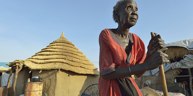 Deep cuts: Achec Teng Wok, who is blind, stands outside her Caritas-built home on March 28 in Abyei, a contested region along the border between Sudan and South Sudan. The Australian Government has reduced its aid budget for Africa by 70 per cent. Photo: CNS/Paul Jeffrey