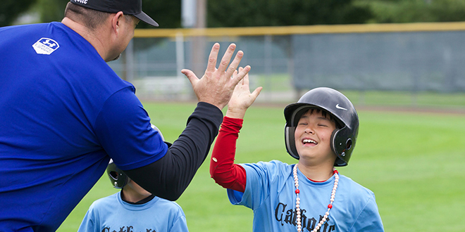 Good sports: A coach congratulates a player during a Catholic baseball camp. Coaches need to show integrity, fairness, patience, joy and kindness, especially toward those who are struggling, Pope Francis said. Photo: CNS photo