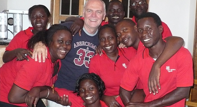 Man of mission: Shayne Bennett with members of a NET Ministries Uganda team; and (inset) spreading the Good News.