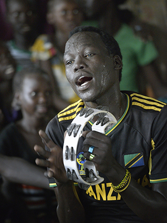 Song of praise: A displaced man sings and plays the tambourine during Mass in a makeshift chapel inside a UN base in Malakal, South Sudan, on April 9. Photos: CNS/Paul Jeffrey
