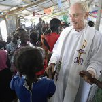 Peace be with you: Maryknoll Father Mike Bassano greets people during the sign of peace at Mass on April 9 in a makeshift chapel inside the Malakal UN base. Photos: CNS/Paul Jeffrey