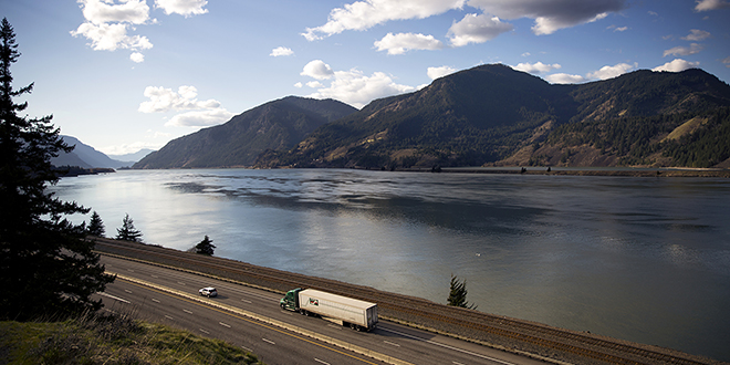 Trucks and cars make their way along the Columbia River in Oregon. Photo: CNS photo/Nancy Wiechec