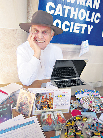 Happy Jesuit: Fr Gregory Jordan was a long-time supporter to Catholic university students; he is pictured here with the Newman Catholic Society stand at the University of Queensland. Photo: Jean Elizabeth Seah.