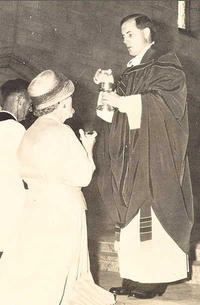 Early days: The Jesuit priest giving Holy Communion to his mother.
