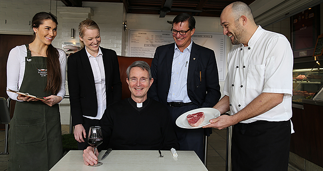 Delicious discount: Norman Hotel staff Lucinda Travers, Julia Ball, owner James Power and chef Frank Correnti ready to serve Brisbane Oratory priest Fr Paul Chandler. Photo: Emilie Ng