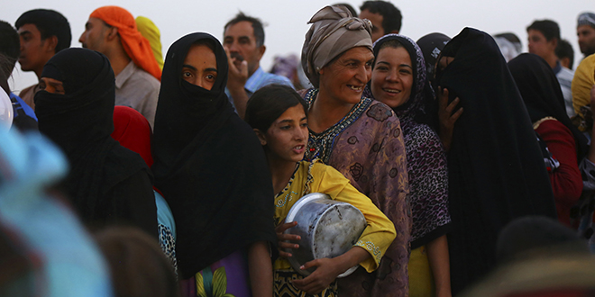 Changing lives: Iraqi refugees line up to receive food inside the Khazer camp on the outskirts of Erbil, Iraq, on June 29. A new Catholic university will be set up in the city with help from Australian Catholic Univeristy and the Australian Catholic Bishops Conference.          Photo: CNS