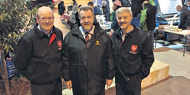 Practical charity: Judge Michael Rackemann (left) and Derek Pingel at a barbecue at The Digger's Rest Park, Goodna, with Ipswich councillor Paul Tully.