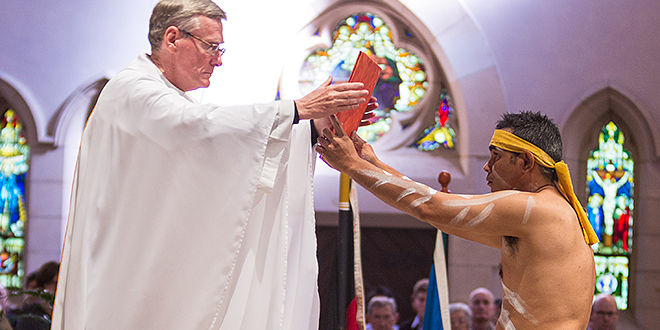 Good News: Fr Gerry Hefferan accepts the Gospel from Marlon Riley during Brisbane's annual National Aboriginal and Torres Strait Islander Week Mass in the Cathedral of St Stephen last Sunday. Photo: Alan Edgecomb