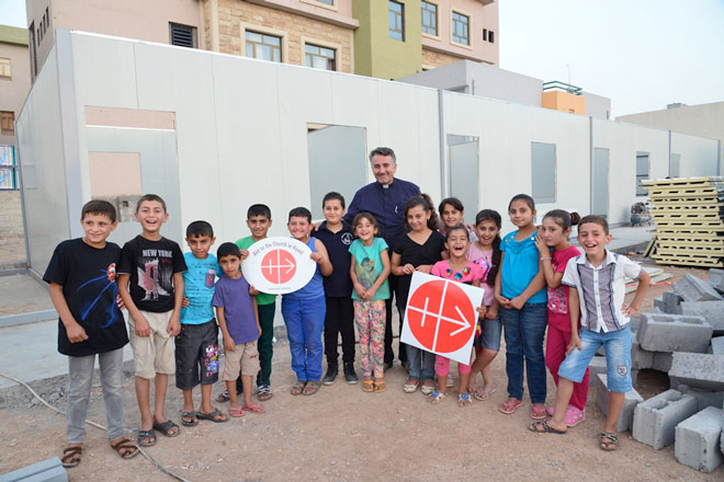 Rebuilding: Fr Douglas Bazi, with a group of children in front of one of the pre-fabricated schools being constructed last year with the assistance of Aid to the Church in Need.