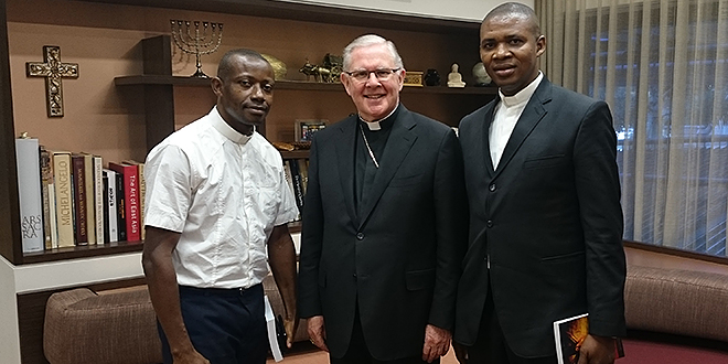 Missionary appointment: Nigerian priests Fr Chukwuemeka Onwubiko (left) and Fr Kevin Njoku (right) are the newest arrivals into Brisbane, pictured here with Brisbane Archbishop Mark Coleridge who will work closely with both.