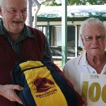Full of life: Fr Jack Agnew (left) presents Percy Bates with a Broncos blanket for his 100th birthday. The blanket was from pastoral carers who visit Percy and other residents at Symes Grove.