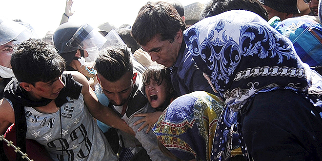 Seeking help: A young girl screams as migrants rush to cross into Macedonia at the Macedonian-Greek border. Catholic aid agencies have urged Europeans not to turn against migrants seeking refuge from Syria and other countries. Photos: CNS