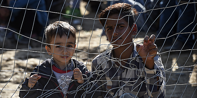 """Offering hope: Migrant children look through a fence as they wait for permission to cross the border between Greece and Macedonia on September 15. """"Do not abandon victims"""" of conflicts in Syria and Iraq, Pope Francis said recently. Photo: CNS"""